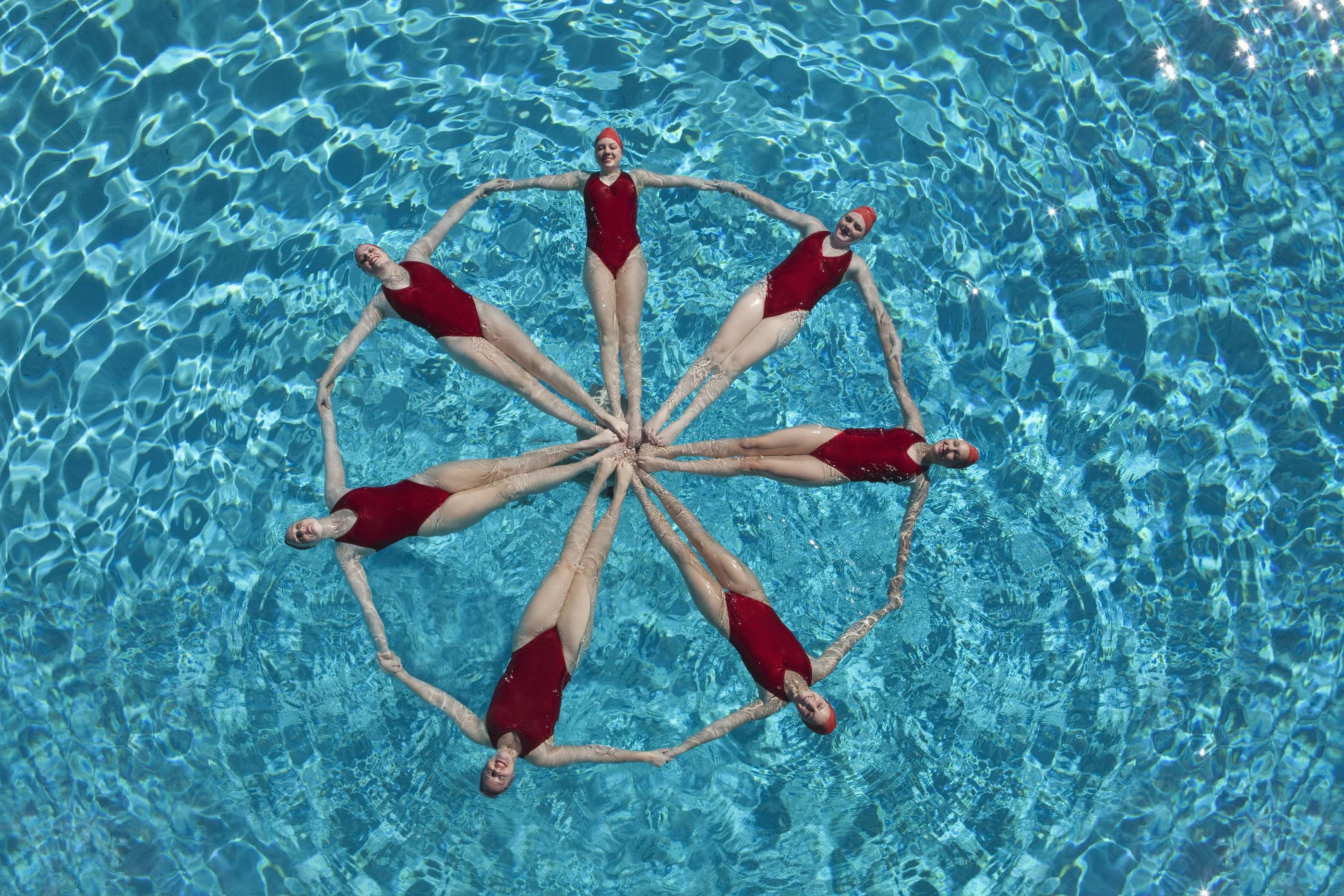 Elevated view of synchronised swimmers forming a circle in pool